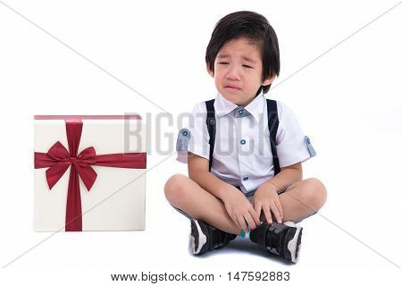 Close up of asian boy sit and crying with gift box on white background isolated.