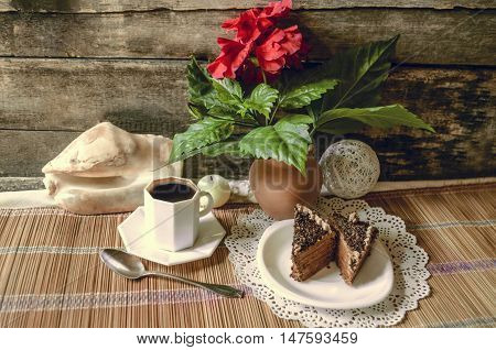 Black coffee, slices of chocolate cake and Chinese rose in the clay pot on straw carpet