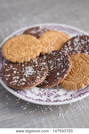 Assorted wheat cookies with chocolate ganache and freshly shredded coconut on a dessert plate, selective focus