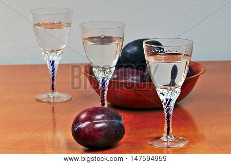 Glasses of homemade plum brandy with plums on a wooden table