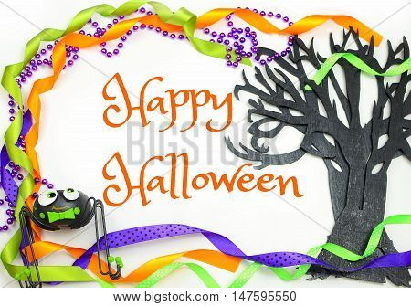 Halloween border of a rough textured wooden cutout of bare tree shape painted black. A silly spider and purple green and orange ribbons and beads frame the Happy Halloween message