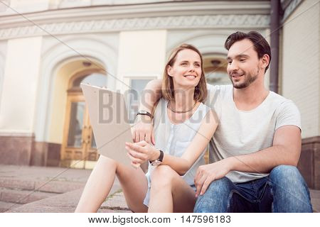 Planning future together. Happy young couple sitting together on the stairs outdoors while holding a clipboard and dreaming about their future