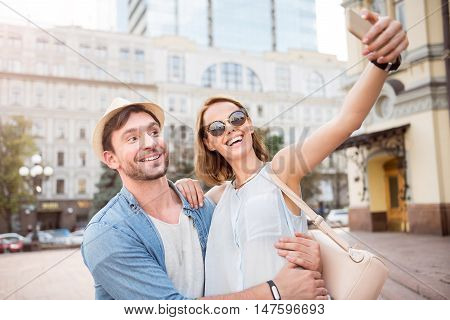 Say cheese. Delighted and positive young tourists couple taking selfie on city street