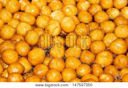 Syrupy friedcakes are being fried in a large frying pan. Also called