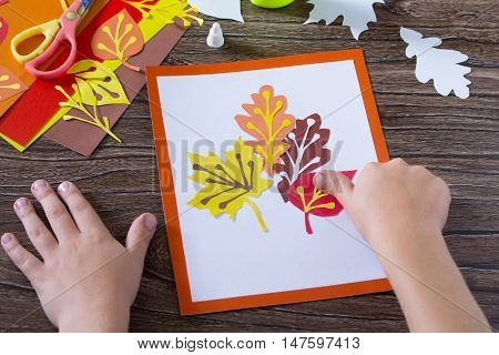Autumn Leaves Of Colored Paper On A Wooden Background. Child Glues The Paper Sheets. Sheets Of Paper