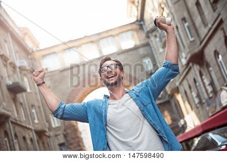 Absolute happiness. Joyful good looking young man walking down the street and holding his hands up while listening to music.
