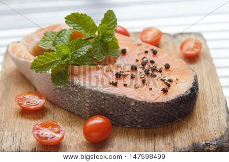 Raw salmon fillet with mint pepper and salt on wooden cutting board
