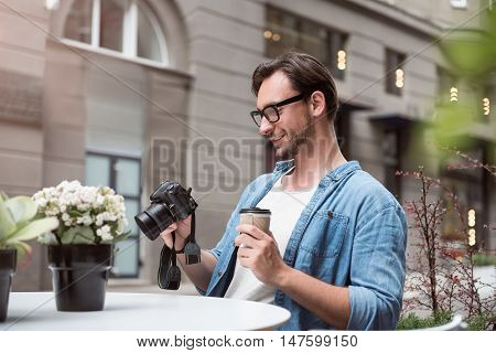 Joyful relaxation. Happy enthusiastic professional photographer looking at the photos and having coffee while sitting at the table