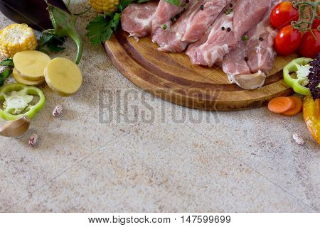 Fresh Raw Meat Pork Tenderloin With Vegetables On A Cutting Board. Stone Background. Copy Space.