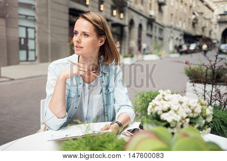 Find out the solutions. Thoughtful nice woman sitting at the table and making notes while concentrating on the project