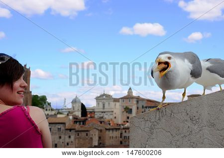 CAPITOLINE HILL, ROME, ITALY - MAY 1, 2014: Seagull and a young unidentified woman against the background of blue sky and the city
