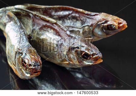 Three dried salt fish closeup on black background