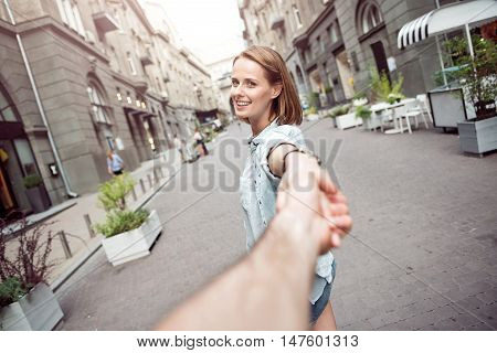 Follow me. Positive delighted nice woman smiling and holding a hand of her boyfriend while having a walk together