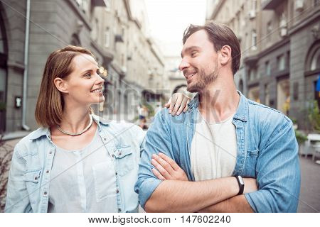 Understand without words. Positive smiling man folding his hands and looking at his girlfriends while standing in the street