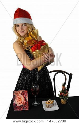 Young attractive snow maiden holds gifts bag with cake dessert and glass wine on table