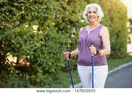 Beautiful aging. Attractive well-fit retiree woman posing with tracking sticks on the trail