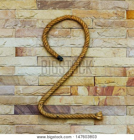 Rope Number two Alphabet on stone background