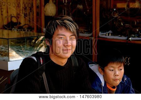 Shu He China - April 26 2006: Young man with an engimatic smile and streaked blond hair with his little brother at a sneaker shop
