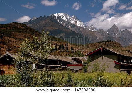 Shu He China - Aoril 20 2006: Naxi farmhouses with tiled roofs sit in the shadow of mighty Jade Dragon Snow Mountain with its snow-capped peaks