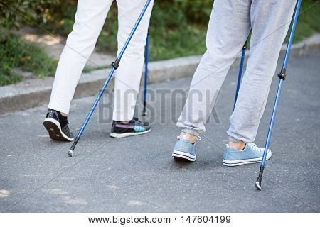 Syncronism. Rear view of two people's legs walking along the road with tracking sticks