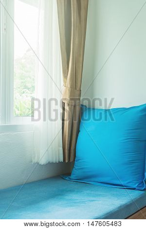 blue pillow near in glass window with soft light in the morning