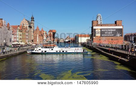 Gdansk, Poland - September 17, 2016: A classic view of the old city of Gdańsk on the Motlawa River. Tourists walk along the   waterfront. On Motlawa green patches of duckweed. Middle of the river flows ship.