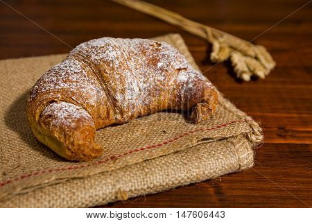Croissant on a burlap and ears of wheat over a table