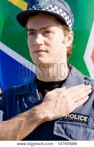 Portrait of Caucasian policeman pledging allegiance with south african flag as background