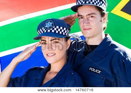 Two police officers saluting in front of south african flag