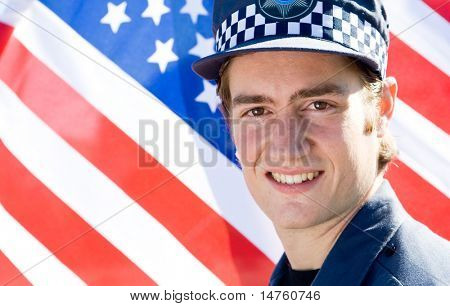 smiling american policeman in front of USA flag