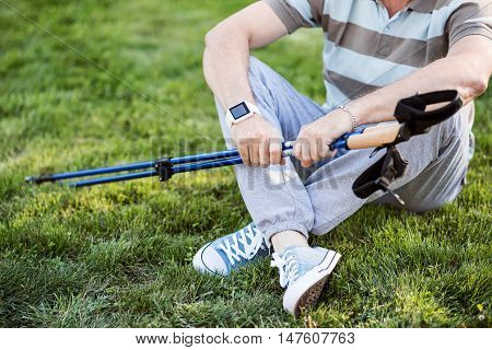 Pause. View of a male body with his legs crossed with a tracking stick in his hands and a fitness tracking watch