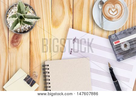 music paper, cactus, fountain pen, tape cassette and coffee latte on wooden table