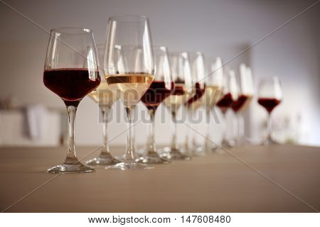 Glasses with red and white wine on table in restaurant