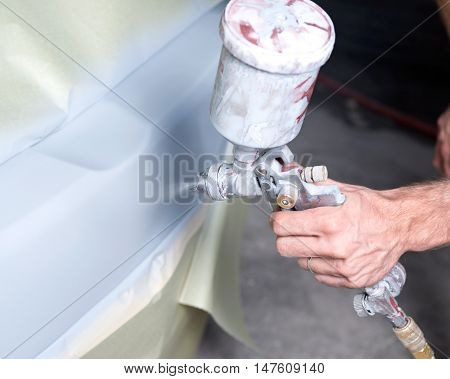 Auto body shop, worker is repainting fixed bumper