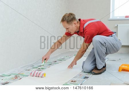 Worker pasting wallpapers. He put glue using a roller.