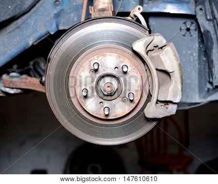 Front disc brake caliper, bracket, rotor of a car after accident on hydraulic lift