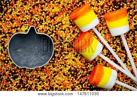 Halloween background - candy corn marshmallow pops on colored sugar sprinkling and cutter pumpkin with space for text