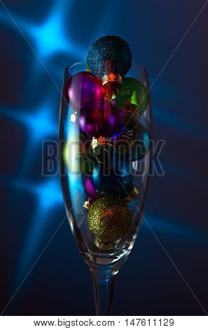 christmas baubles in wineglass on a dark background.