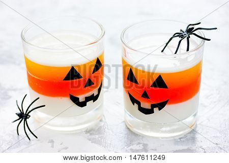Candy corn layered jello - sweet treat for children on Halloween. White yellow and orange jelly in glasses on a white background