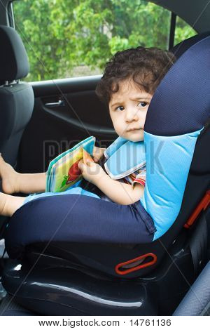 toddler baby boy reading in car seat