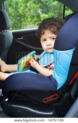 toddler baby boy reading in car seat
