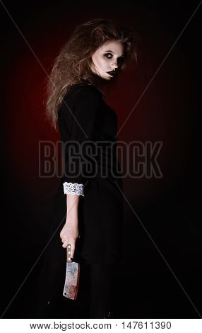 Horror shot: a scary evil girl with bloody cleaver in hands