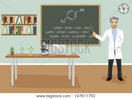 mature male teacher giving a lecture in chemistry class next to blackboard