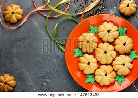 Homemade gingerbread cookie for Halloween or Thanksgiving. Pumpkin cookies for kids on orange plate blank space for text top view
