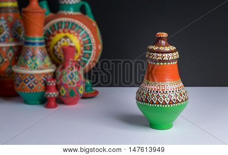 Still life of one ornate colorful pottery vase on background of blurred group of colorful vases white table and black wall