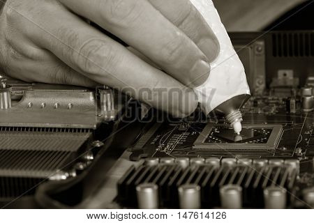 computer repair. black and white image men's fingers squeezed from a tube of thermal paste to the video processor. close-up selective focus