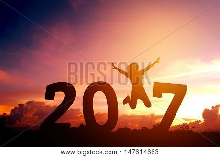 Silhouette young woman jumping to 2017 new year