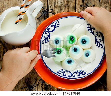 Child eating sweet eyeball jelly funny Halloween dessert