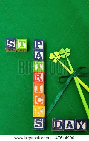 St Patrick's day spelled with colorful alphabet blocks displayed with two four leaf clovers on a green background