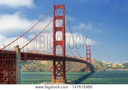 The iconic golden gate bridge over San Francisco Bay with the Marin Headlands in the background on a sunny blue sky day.